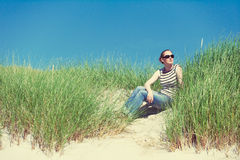 Young woman sitting in sand dunes amongst tall grass in Luskentyre, Isle of Harris, Scotland. Young woman sitting in sand dunes amongst tall grass relaxing stock photography