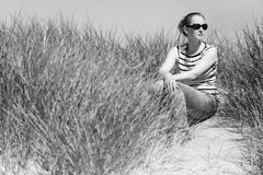Young woman sitting in sand dunes amongst tall grass relaxing, enjoying the view on sunny day Stock Photo