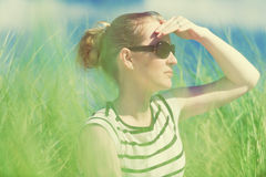 Young woman sitting in sand dunes amongst tall grass relaxing, enjoying the view on sunny day royalty free stock images