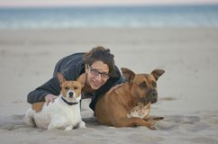 Young woman sitting on the sand with her dogs on a beach.  royalty free stock photography