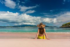 Young woman sitting on the sand at Pink Beach in Komodo Island stock photos