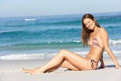 Young Woman Sitting On Sandy Beach. On Holiday Wearing Bikini Stock Photography
