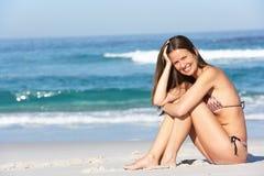 Young Woman Sitting On Sandy Beach. On Holiday Wearing Bikini Royalty Free Stock Photography