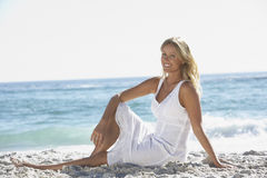 Young Woman Sitting On Sandy Beach Stock Image