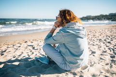 Young woman sitting on sandy beach looking at waves. Side view. Female with red curly hair wearing denim jacket and blue jeans resting on seashore at sunny day stock images