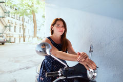 Young woman sitting on the scooter Royalty Free Stock Images