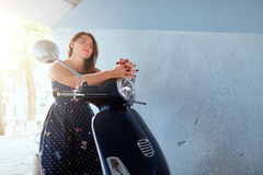 Young woman sitting on the scooter Stock Photography