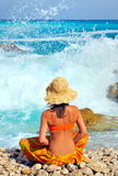 Young woman sitting by the sea Stock Photos