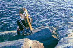 Young woman sitting by the sea Stock Image