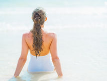 Young woman sitting on sea coast. rear view Royalty Free Stock Image