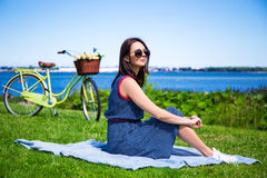 Young woman sitting on the sea coast with vintage bicycle Royalty Free Stock Image