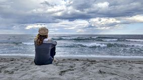 Young woman sitting by the sea with stormy sky, looks at the horizon thoughtfully stock image