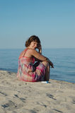 Young woman sitting on the seashore Royalty Free Stock Photos