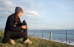 Young Woman Sitting at the Seaside Holding a Vintage Camera Stock Images