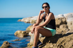 Young woman sitting on seaside rock thinking Royalty Free Stock Photos