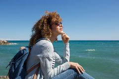 Young woman sitting by seaside thinking. Portrait of young woman sitting by seaside thinking Royalty Free Stock Photography