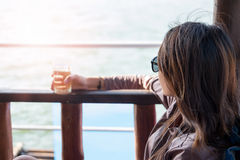 Young woman sitting seat on boat while drinking water viewing sc Stock Photos