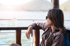 Young woman sitting seat on boat while drinking water viewing sc Royalty Free Stock Images