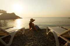 Young woman is sitting on the shore with beach dress and a straw hat on. Back view portrait of pretty girl relaxing near. The sea in tender morning sun Stock Photo