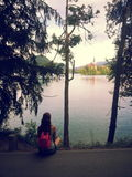 Young woman sitting at the shore of Lake Bled stock image