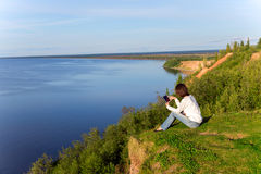 Young woman sitting on the shore of the lake with tablet compute Stock Images