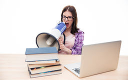 Young woman sitting and shouting in megaphone Royalty Free Stock Photo