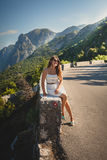 Young woman sitting on side of the high mountain road at sunny d Stock Images