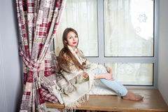 Young woman sitting on sill Stock Images