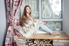 Young woman sitting on sill Royalty Free Stock Photo