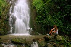 Young woman sitting at Simangande falls on Samosir island, Sumat Royalty Free Stock Photography