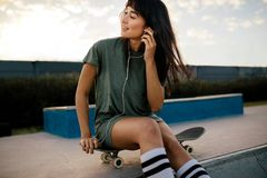 Woman relaxing at skate park listening music. Young woman sitting on the skateboard adjusting her earphones at the skate park. Urban girl relaxing at skate park Stock Photos