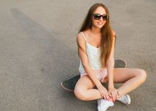 Young woman sitting on the skateboard Royalty Free Stock Photography