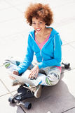 Young woman sitting on skateboard with laptop Stock Images