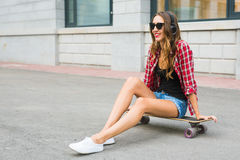 Young woman sitting on the skater. Smiling woman with skateboard in outdoors Royalty Free Stock Photos
