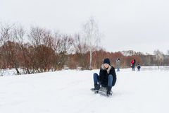 Young woman sitting on sledge in the snow Stock Images