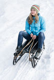 Young woman sitting on a sledge in the snow Stock Photos