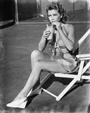 Young woman sitting on sling chair, sipping a drink stock photo