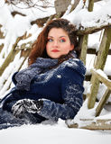 Young woman sitting in the snow. Portrait of a beautiful 20 year old woman sitting in the snow in winter Royalty Free Stock Image