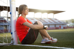Young Woman sitting on a soccer field Royalty Free Stock Images