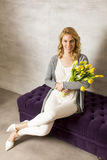 Young woman sitting on the sofa with a bouquet of yellow tulips Royalty Free Stock Photography