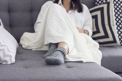Young woman sitting on sofa covered in blanket, focus on her grey socks. Young woman sitting on the sofa covered in blanket, focus on her gray socks Royalty Free Stock Photo