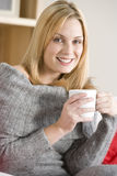 Young Woman Sitting On Sofa With Cup Of Coffee Stock Photo