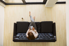 Young woman sitting on a sofa with digital tablet surfing online Stock Photo