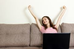 Young woman sitting on a sofa with her laptop computer raised her hands in the air, happiness and success concept royalty free stock photos