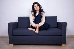 Young woman sitting on sofa at home Royalty Free Stock Photos