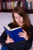 Young woman sitting on sofa at home, reading a book Royalty Free Stock Photos