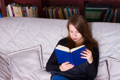 Young woman sitting on sofa at home, reading a book Royalty Free Stock Images