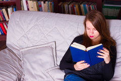 Young woman sitting on sofa at home, reading a book Stock Photos