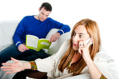 Young woman sitting on sofa at home, talking on a mobile whilst her boyfriend reads Royalty Free Stock Image