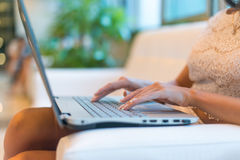 Young woman sitting on sofa at hotel lobby working laptop computer Stock Photography